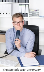 Young businessman with glasses is holding a telephone receiver and a pen while sitting at the desk in the office.