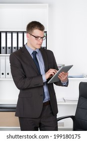Young businessman with glasses is using a tablet while standing in front of a shelf in the office. The man is looking to the tablet.