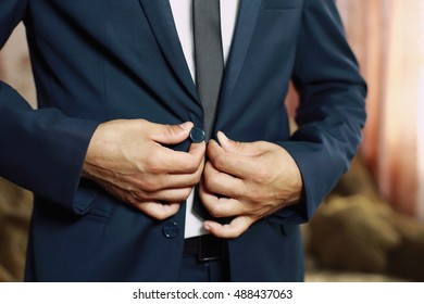 Young businessman or groom fasten button of his grey blue jacket with grey tie