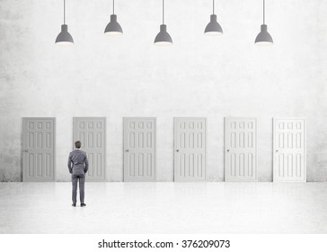A young businessman with hands in pockets standing in a room with numerous closed doors. Five lamps above. Back view. Concrete background. Concept of finding a way out.