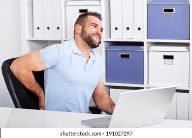 Young businessman has backache at work with a laptop in the office