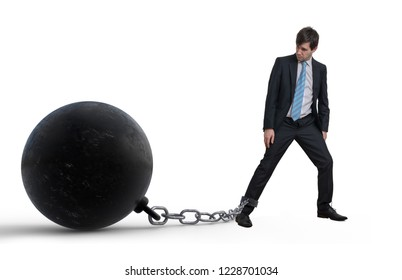 Young businessman has chained big metal ball to his leg. Isolated on white background.