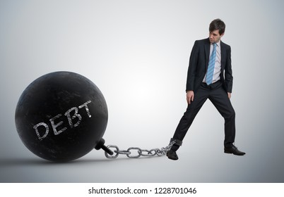 Young businessman has chained big metal ball to his leg with debt written.