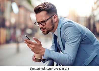 Young businessman have break,drink coffee and using mobile phone outside.