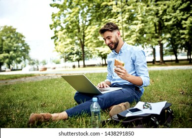 Young businessman having sandwich for lunch in the park and working on laptop