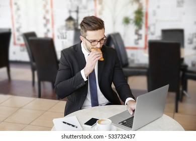 Young businessman having snack while working with laptop in cafe