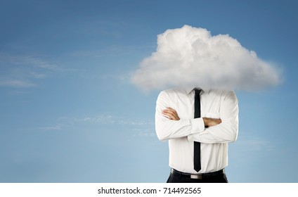 Young businessman with head in the clouds over blue sky background with copy space
