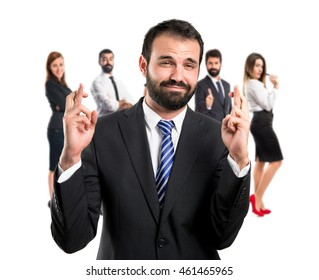 Young businessman with his fingers crossing with many people behind