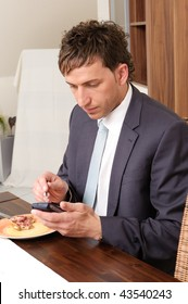 Young businessman with his smartphone (cell) at the breakfast