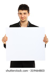 Young businessman holding blank board and looking at the camera. Isolated on white background