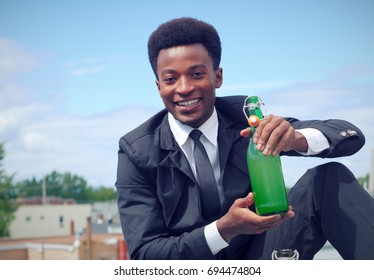 young businessman holding bottle of wine on a roof wearing suit and tie