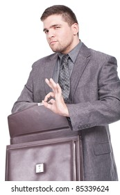 young and businessman holding a briefcase and making ok sign