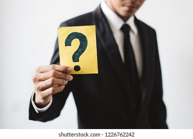 Young businessman holding a card with QUESTION MARK. Concept of Business Strategy, solution and problem