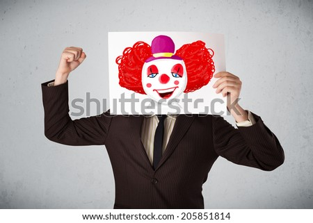 Young businessman holding a cardboard with a clown on it in front of his head