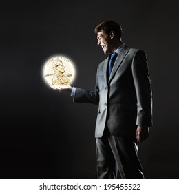 Young businessman holding cent coin in palm