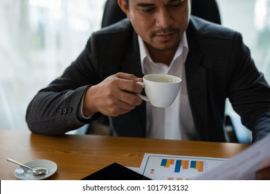 Young businessman holding a coffee cup in hand, looking at the financial statements of the Company in the document shown as a graph. Concept Marketing Investment