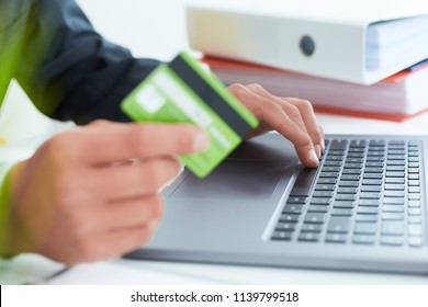 Young businessman holding a credit card and typing. On-line shopping on the internet using a laptop. Just hands over the table.