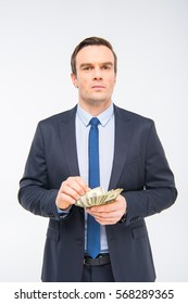 Young businessman holding dollar banknotes isolated on white
