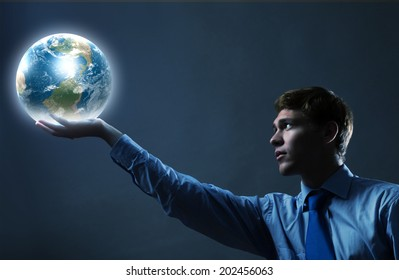 Young businessman holding Earth planet in hand. Elements of this image are furnished by NASA