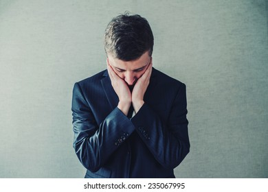 Young businessman holding head in his hands