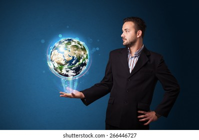 Young businessman holding in his hand a glowing earth globe, Elements of this image furnished by NASA