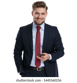 Young businessman holding his phone and one hand in his pocket while smiling to the camera and wearing a blue suit, standing on white studio background