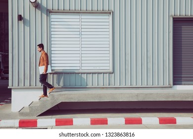 Young businessman holding laptop walking down the stairs with failing, copy space, process color.