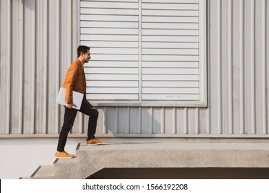 Young businessman holding laptop walking up the stairs with success, copy space, process color.