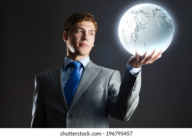 Young businessman holding moon planet in hand