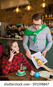 Young businessman holding paper with graphs, standing near woman in cafe