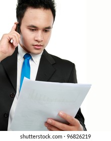 Young businessman holding a report and talking to mobile phone