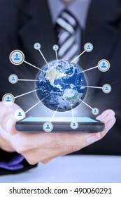 Young businessman holding smartphone with 3d earth globe and social media icon.  Elements of this image furnished by NASA