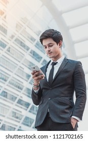 Young businessman holding smartphone for business work at urban city with skyscrapers buildings in the background.Businessman using mobile phone app texting outside of office.