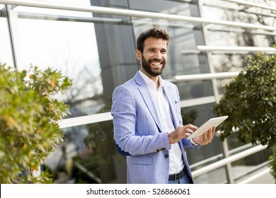 Young businessman holding tablet in hands outdoor