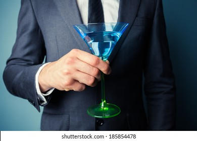 Young businessman is holding a tall cocktail glass
