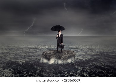 Young businessman holding umbrella while standing on the rock over ocean