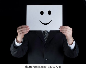 Young businessman holding white card with a happy face on it isolated on black background