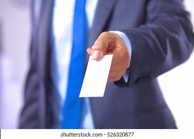 young businessman holds out his hand with a business card