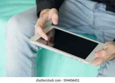 Young businessman holds and touch tablet, while sitting on the bed