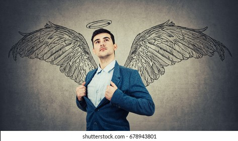 Young businessman imagining himself as an angel with wings sketch behind his back and a halo above head. Super power idea, self development, success and freedom concept isolated on grey.