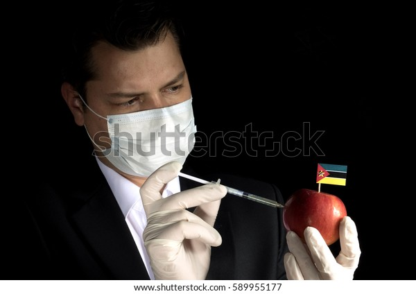 Young businessman injecting chemicals into an apple with Mozambique flag on black background
