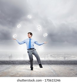 Young businessman juggling with currency symbols against city background