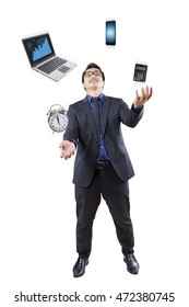 Young businessman juggling in the studio with business items like laptop, cellphone, calculator, and alarm clock
