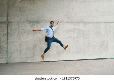 Young businessman jumping in joy and looking at camera outdoors in the city