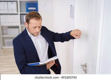 Young businessman knocking on the door of the boss as he stands outside looking down at a folder in his hand
