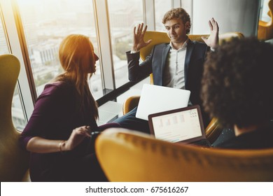 Young businessman with laptop is angry, annoyed, impatient and giving up during his meeting with two businesswomen on yellow armchairs near big window of office skyscraper with cityscape outside