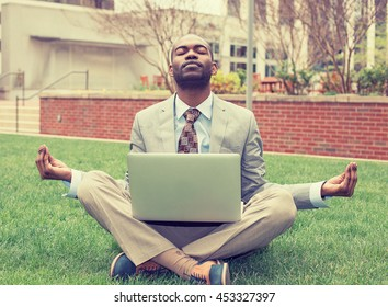 Young businessman with laptop meditating in lotus pose taking a deep breath outside corporate office. Business yoga and stress free environment. Peace of mind concept