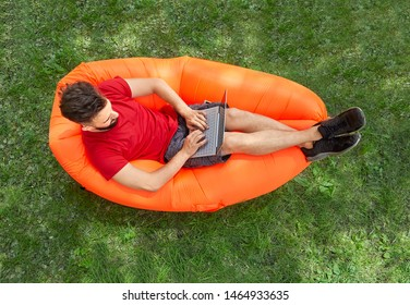 Young businessman with laptop on his knees is lying on the orange inflatable lounger on the grass in forest and relaxing.