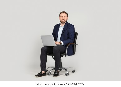 Young businessman with laptop sitting in comfortable office chair on grey background