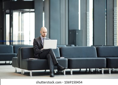 Young businessman with laptop sitting on black leather sofa in airport lounge and networking